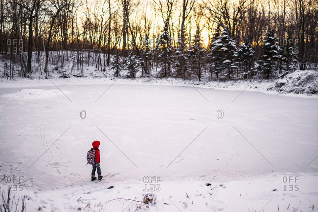 Young boy walking alone in the snow
