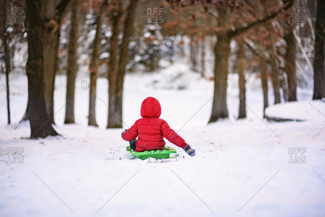 Child sliding down a hill on a sled