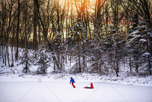 Child pulling a friend in a sled on a frozen lake