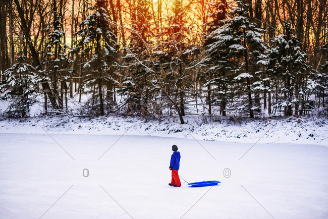Child walking on a frozen lake with his sled
