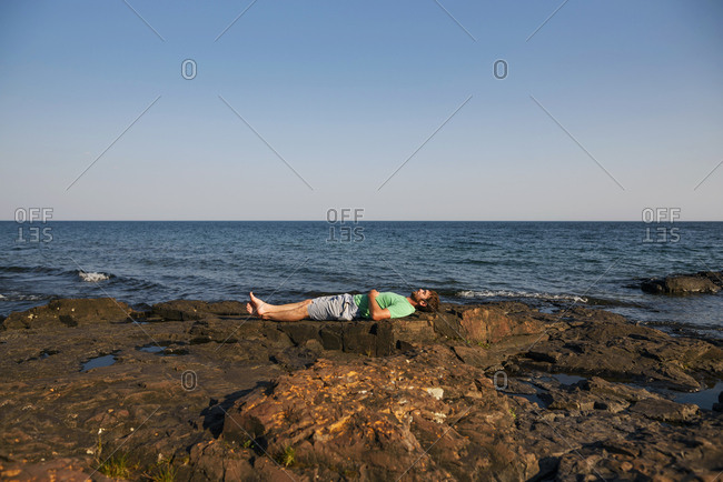 Man lying on a rocky shoreline