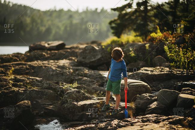 Young boy exploring a rocky shoreline