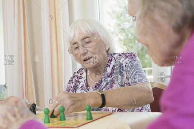 Senior women playing board game in rest home