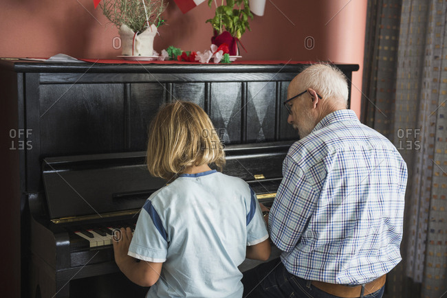 Grandfather and grandson playing piano instrument