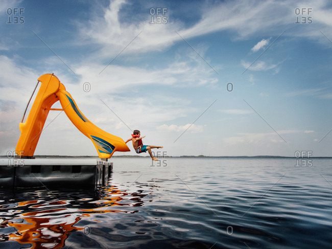 Boy flying off slide into lake