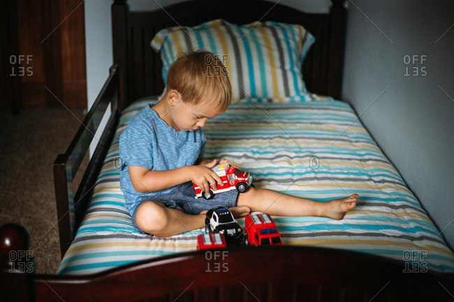 Boy plays with toys on his bed