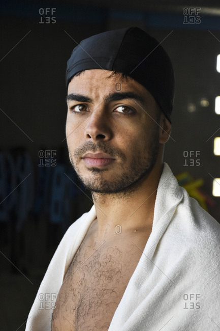 Young sportsman in towel looking at camera at swimming pool.