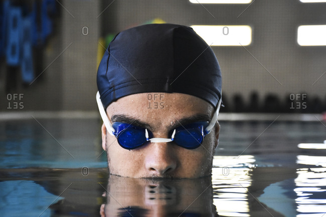Man in swimming cap and goggles swimming in pool.