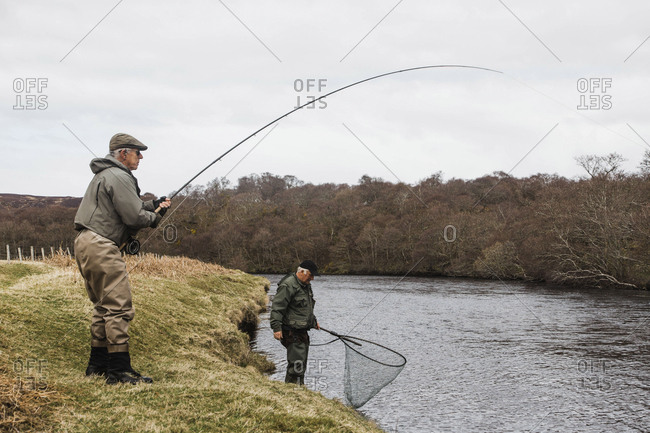 Bettyhill, Scotland - April 22, 2017: Two fly fisherman on a riverbank near Bettyhill, Scotland
