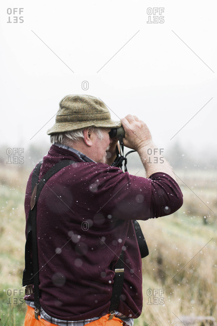 Scotland, United Kingdom - April 24, 2017: An older man looks through binoculars on a farm while it snows