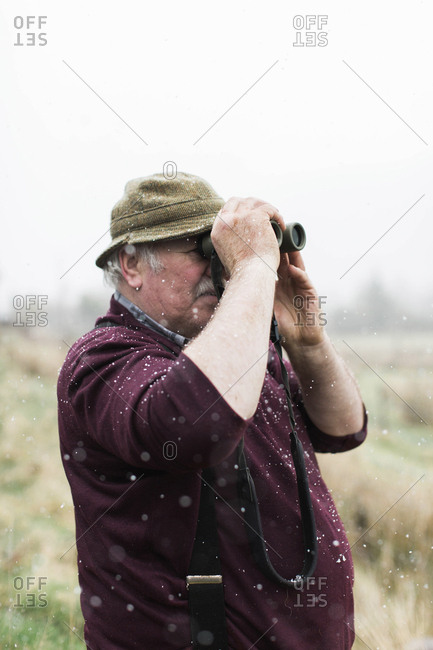 Scotland, United Kingdom - April 24, 2017: Senior man looks through binoculars on a farm while it snows