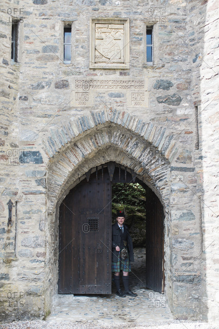 Isle of Skye, Scotland - April 24, 2017: Scottish man at the entrance of the Eilean Donan Castle near the Isle of Skye, Scotland