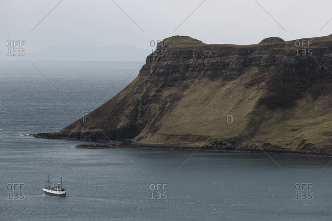 Isle of Skye, Scotland - April 25, 2017: A boat moves through calm waters off the north coast of the Isle of Sky, Scotland