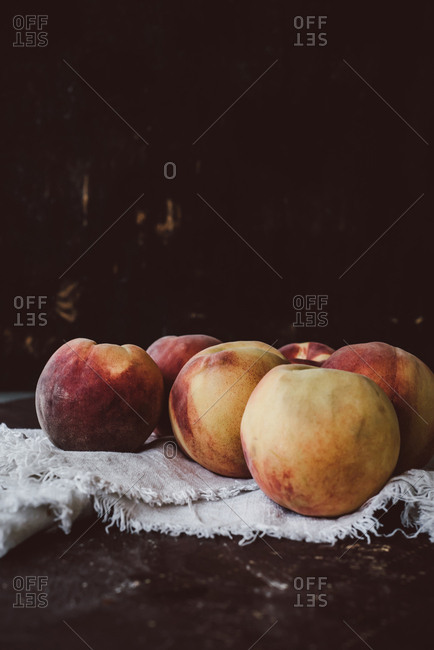 Fresh peaches on a white towel