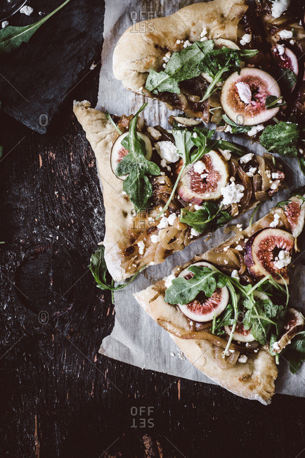 Pizza slices with fig jam, goat cheese and arugula