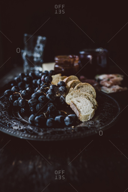 Grapes and bread on a serving platter with jam in the background