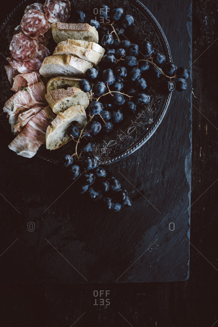 Grapes, meat and bread on a serving platter