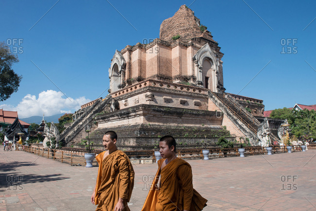 Chiang Mai, Thailand - November 30, 2017: Monks walking by the Wat Chedi Luang temple in Chiang Mai, Thailand