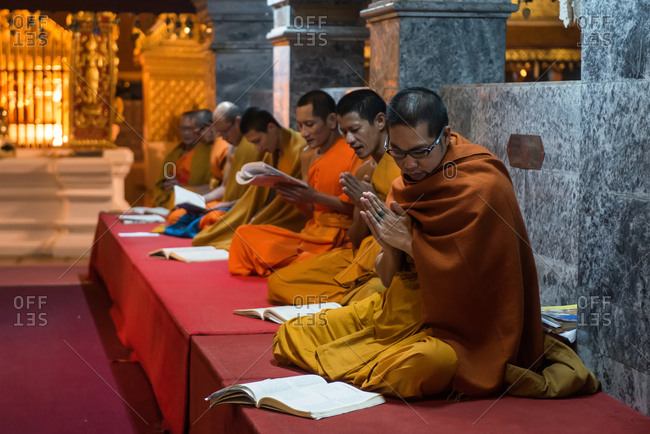 Chiang Mai, Thailand - November 30, 2017: Monks praying in the Wat Phra Singh temple