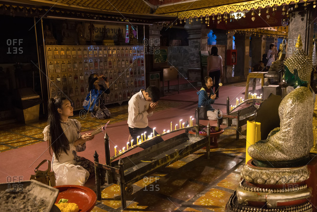 Chiang Mai, Thailand - November 30, 2017: People praying in the Wat Phra Singh temple