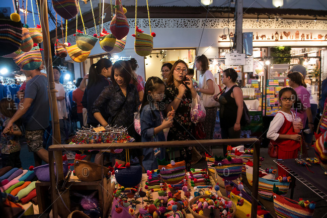 Chiang Mai, Thailand - December 3, 2017: Shoppers looking at colorful purses for sale at market
