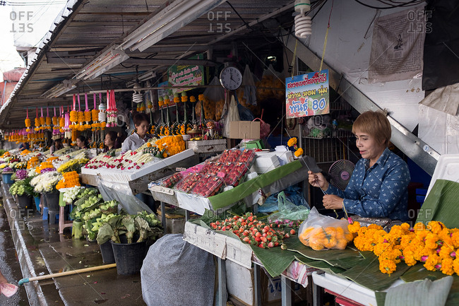 Chiang Mai, Thailand - December 3, 2017: Woman selling flowers at a market in Thailand