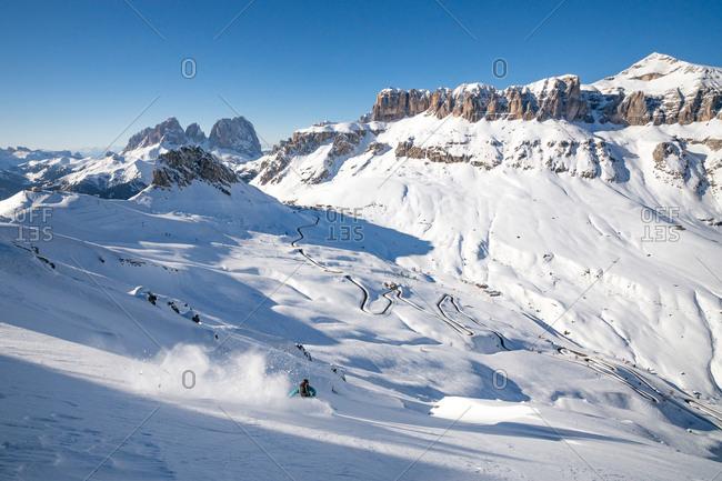 Belluno, Italy - March 23, 2014: A skier is enjoying fresh powder snow in a valley in the Italian Dolomites