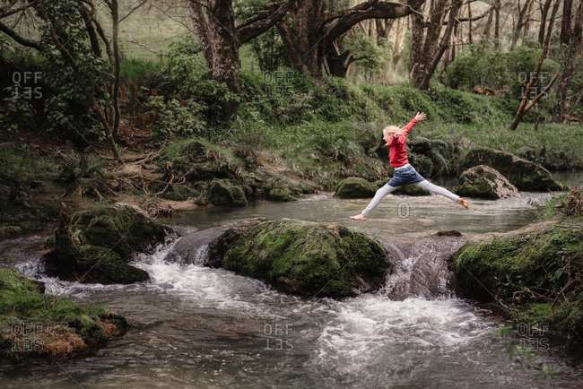 Girl leaping on mossy rocks while crossing a river