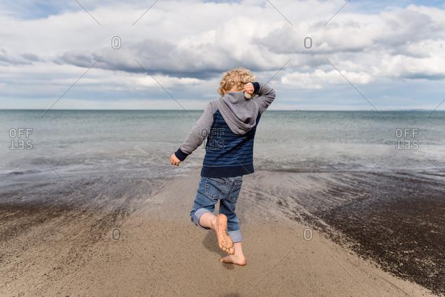Boy throwing stones on sandy beach in New Zealand