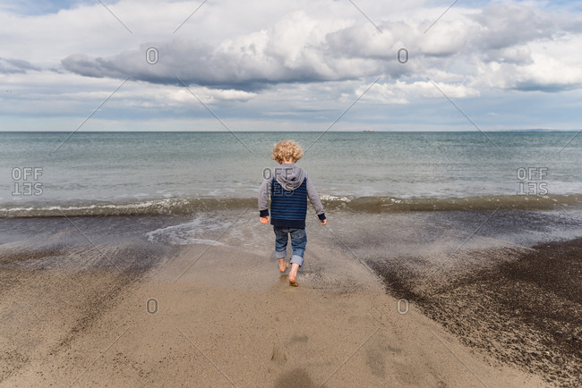 Boy walking barefoot on sandy beach in New Zealand