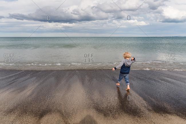 Boy throwing rocks on sandy beach in New Zealand
