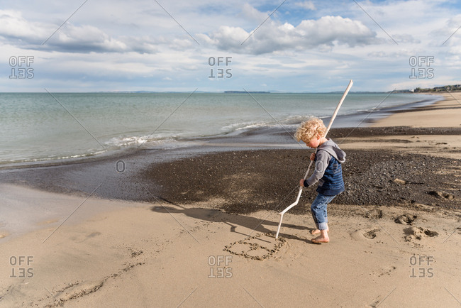 Boy writing in sand with a stick on a beach in New Zealand