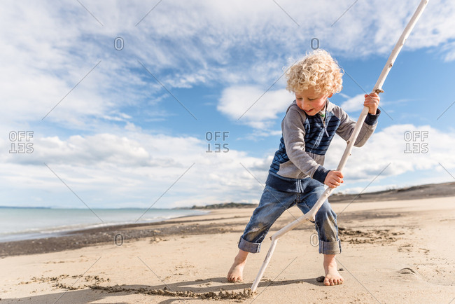 Boy drawing in sand with a stick on a beach in New Zealand