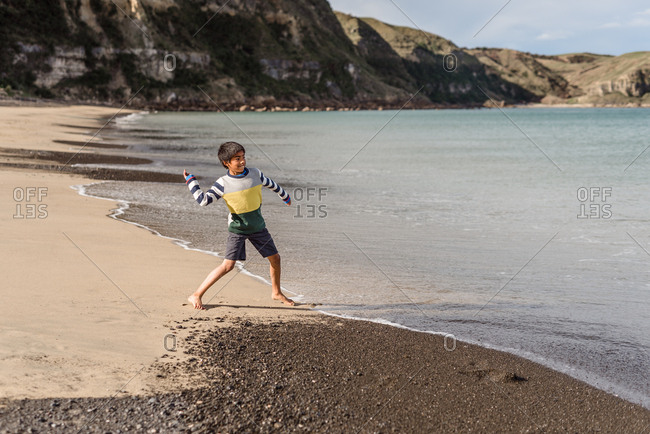 Young boy throwing rocks on sandy beach in New Zealand