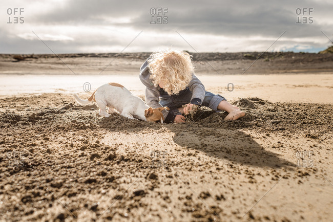Boy digging with his dog on a sandy beach
