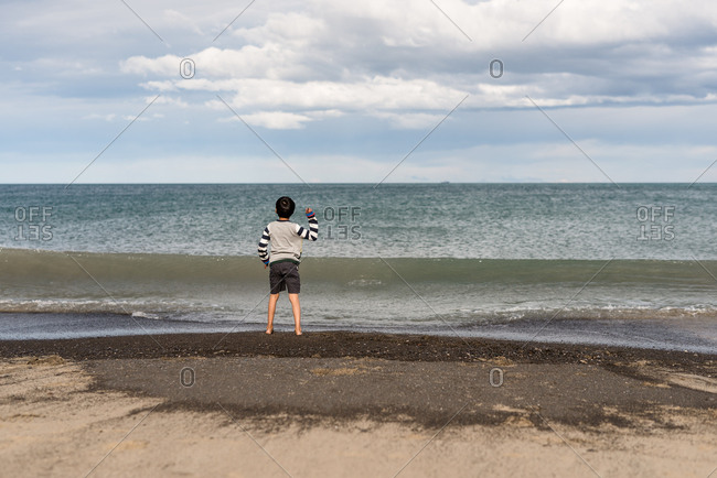 Rear view of boy throwing rocks on sandy beach in New Zealand