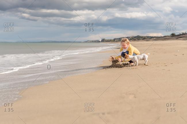 Girl building sand castle with her dog on a sandy beach
