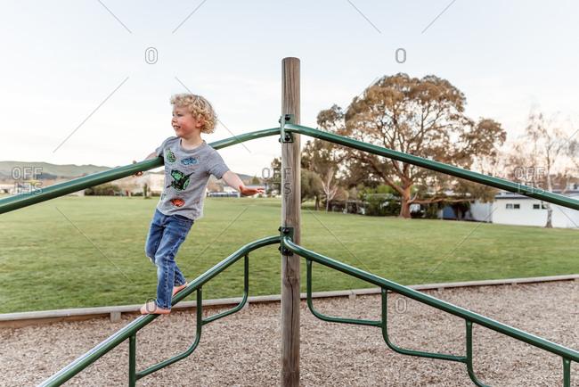 Barefoot boy playing on playground