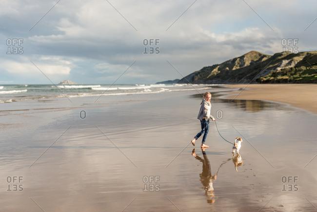 Girl walking her dog on a sandy beach