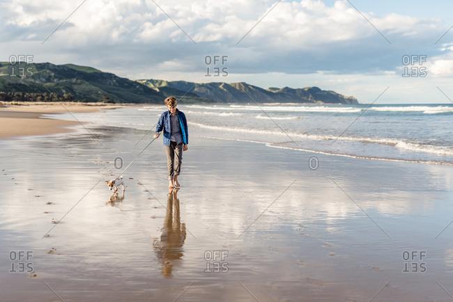 Boy walking his dog on a sandy beach