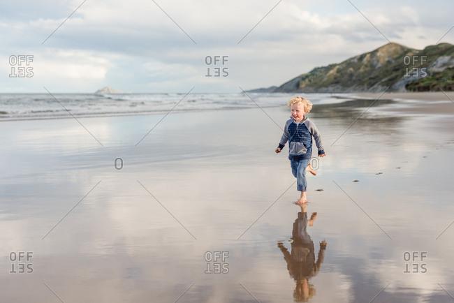 Boy walking barefoot on a beach in New Zealand