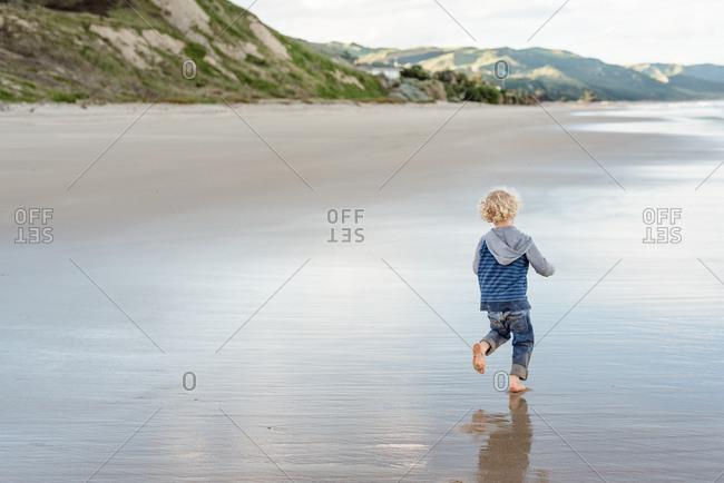 Rear view of boy walking barefoot on a beach in New Zealand