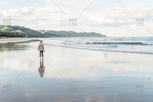 Rear view of girl walking barefoot on a beach in New Zealand