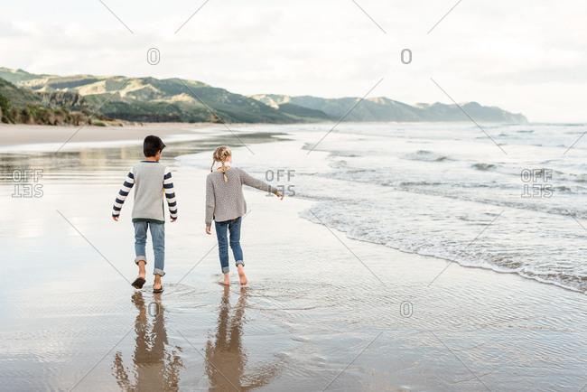 Two kids walking barefoot by the ocean