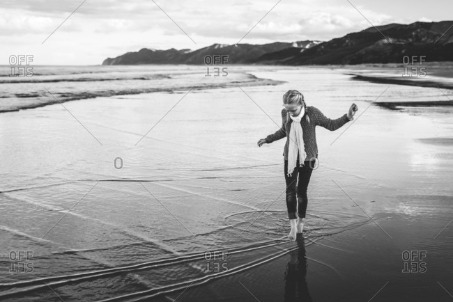 Girl walking barefoot on a beach in New Zealand in black and white
