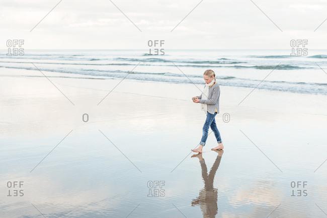 Girl walking barefoot on a beach in New Zealand