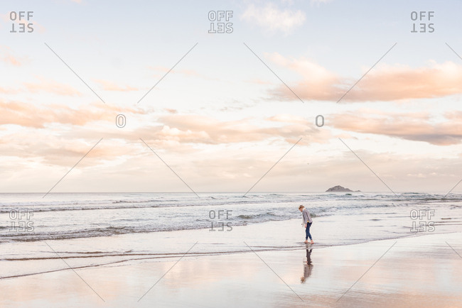 Girl on a beach in New Zealand at sunset