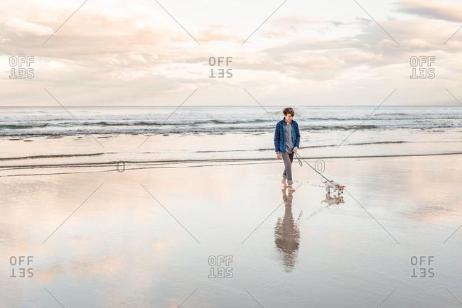 Teen boy walking his dog on a sandy beach