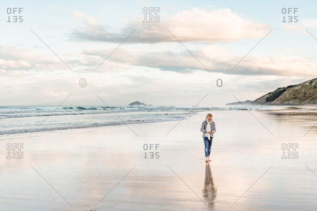 Young girl walking barefoot on a beach in New Zealand