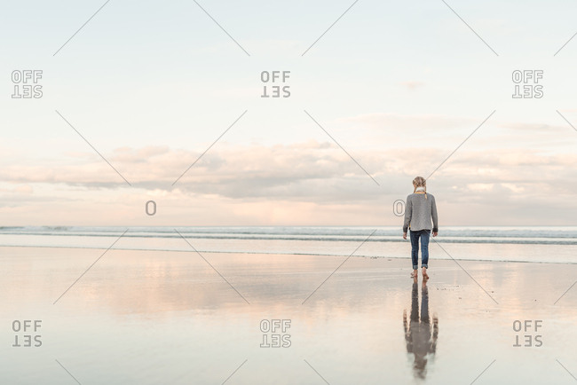 Rear view of girl walking barefoot on a beach in New Zealand at sunset